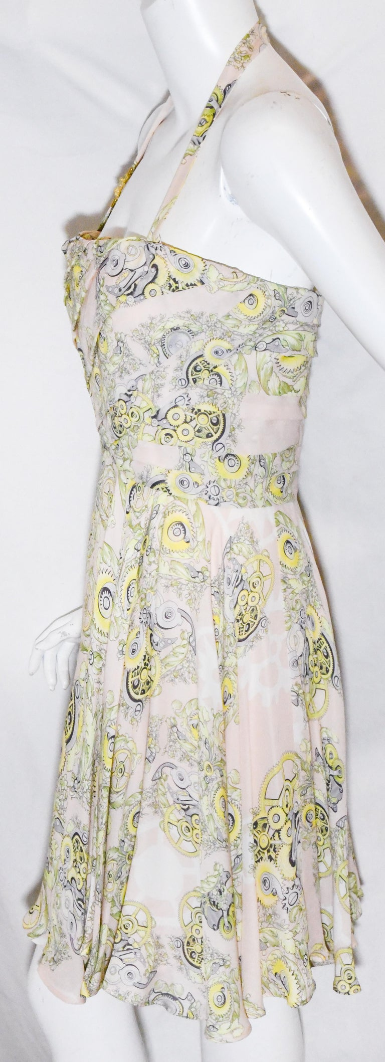 Versace Collection halter top dress includes decorative brooch on shoulder strap.  This flirty summer style dress  is a softer side to the Versace House criteria.   The print combines the mechanical features with beautiful flowers. It is a short