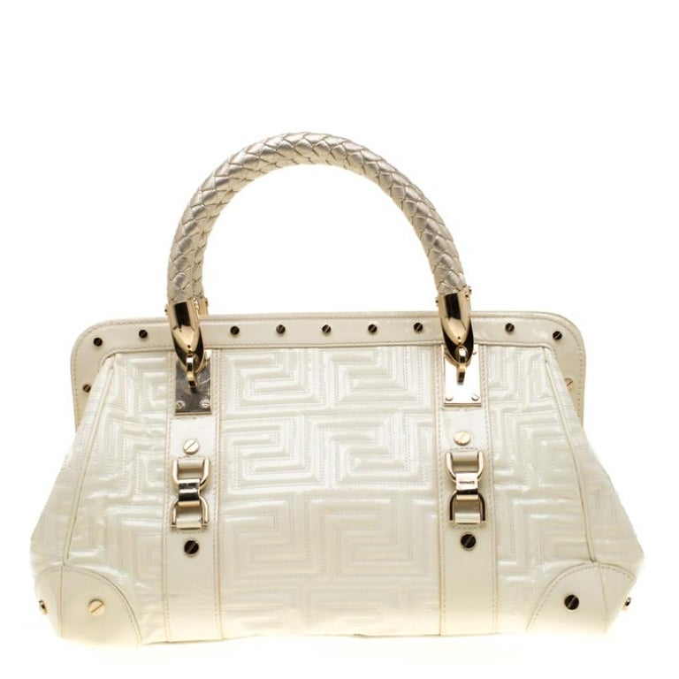 This eye-catching Versace Snap Out Of it satchel is sure to make heads turn. Crafted from cream quilted leather, the bag is accented with a Gianni Versace Couture plate and gold-tone studded hardware. It features dual top braided handles and a top