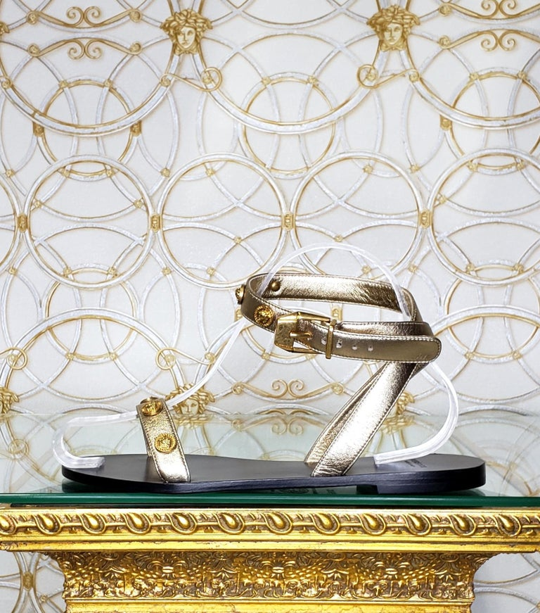 VERSACE   Gold Ankle strap sandals  Medusa gold metallic studs, open round toe, buckle fastening ankle strap.  Content: 100% leather   IT Size 36.5 - US 6.5 insole: 9 1/2