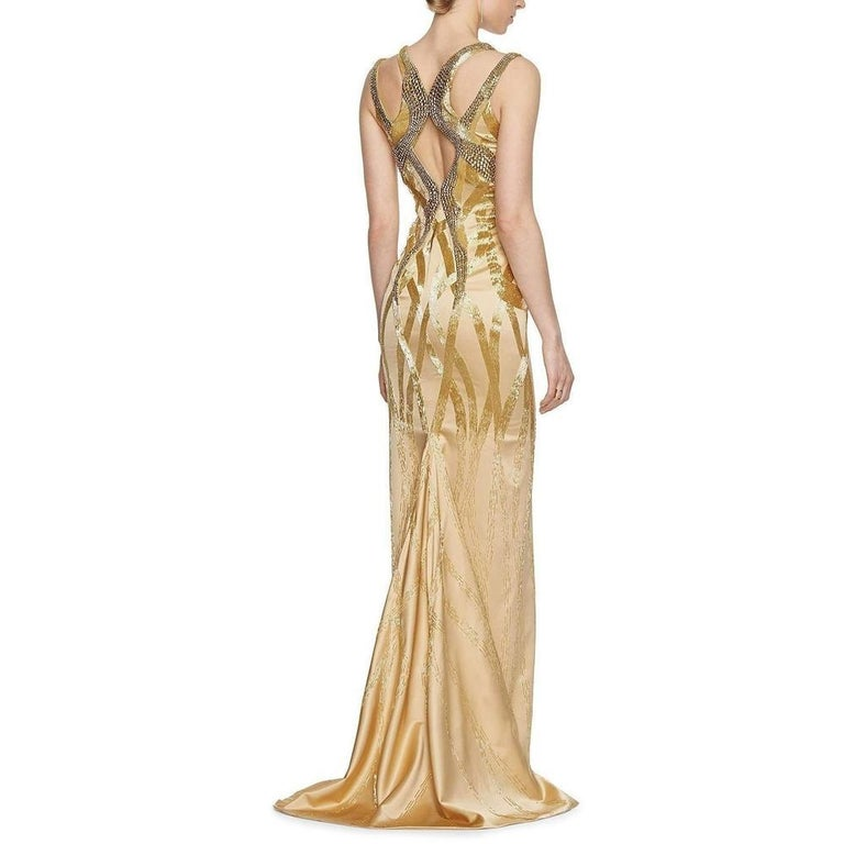 The Versace fashion house captures luxury, splendor and glamour in a collection piece worthy of your most special occasions. Faceted stones set off the dazzling bodice of this satiny silk dress, interlaced with thousands of sequins that delicately