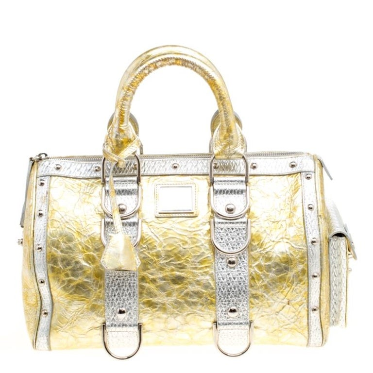 This bold and eye-catching Versace Snap Out Of it satchel is sure to make heads turn. Crafted from ceramic effect leather the bag is accented with a Gianni Versace Couture plate and silver-tone studded hardware. It features dual top handles and a