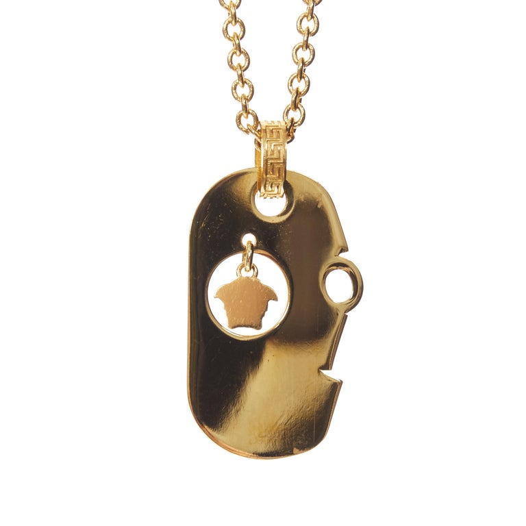 VERSACE gold tone nickel Love hanging Mesuda dog tag plate necklace  Brand: Versace Designer: Donatella Versace Model Name / Style: Dog tag necklace Material: Nickel Color: Gold Pattern: Solid Closure: Buckle Extra Detail: Gold-tone nickel. Love