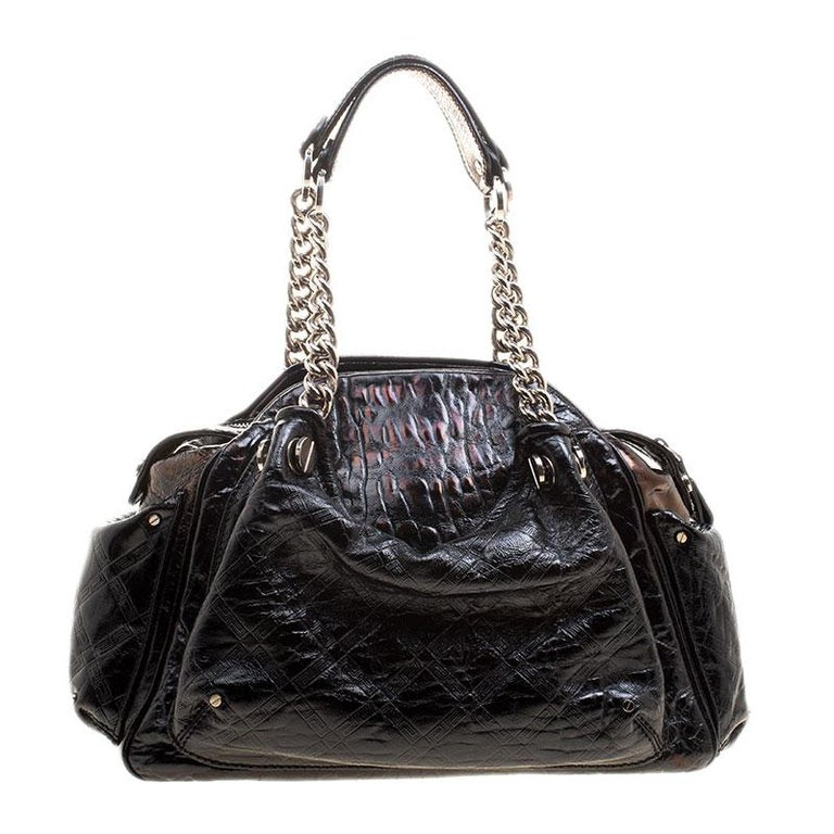 Crafted in black patent leather and accented with silver tone hardware details, this satchel from Versace is perfect for everyday and casual use to carry all your essentials with you. Featuring a quilted design on the surface and a V charm, this bag