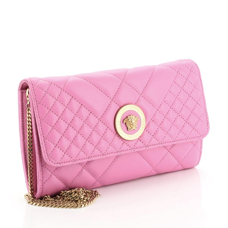 This Versace Icon Wallet on Chain Quilted Leather, crafted in pink quilted leather, features a chain shoulder strap, flap top with Medusa head medallion and gold-tone hardware. Its snap closure opens to a pink leather interior with multiple card