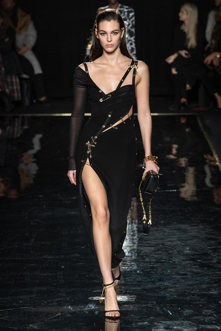 Offered brand new Versace's current version of the safety pin dress.   Fashioned of a substantial black silk crepe strategically adorned with Versace signature safety pins.  Dress is fully lined and features the Versace iconic body suit to adjust