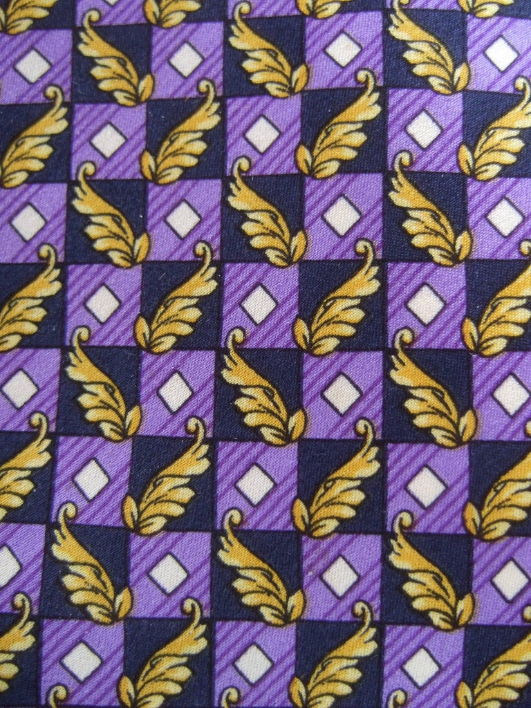 Versace Italian violet and gold graphic print silk necktie c 1990s The stylish designer necktie is illustrated with violet color block graphics juxtaposed with golden leaf foliage   The geometric box design is contiguous on the front Transitions