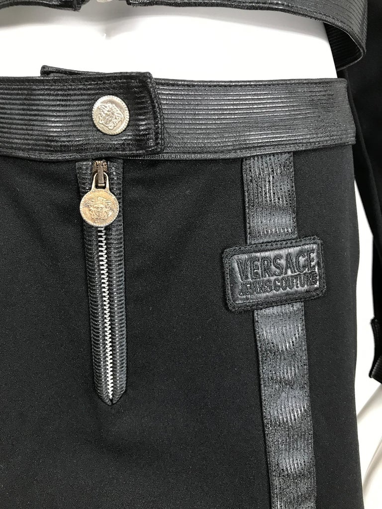 Versace Jeans Couture black vinyl and stretch fabric cropped jacket & skirt from the 1990s. Black jeans style jacket closes at the front with a zipper and Medusa head round pull, the jacket has a black vinyl collar, black vinyl cuffs that close with