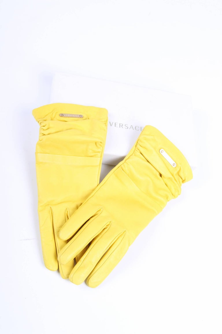 Outstanding pair of gloves by Versace crafted in bright yellow leather.  Embellished with pleats and a light gold-tone plaque with Versace logo. Lining in 100% silk in a beige color.  New! Comes with little box.  Size: S  Made in Italy.