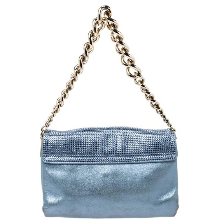 This Sultan shoulder bag from Versace is a fabulous piece. The bag comes in a luxurious light blue exterior made from crystal embellished shimmer leather and designed with the signature Medusa motif on the front, a gold-tone chain handle, and