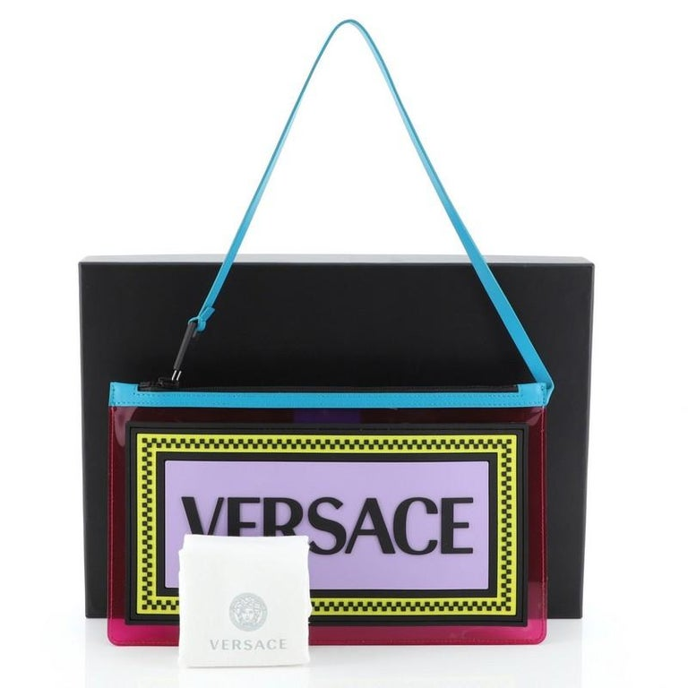 This Versace Logo Clutch PVC, crafted from pink PVC, features a top handle attached to zip fastening and black-tone hardware. Its zip closure opens to a pink PVC interior.   Condition: Excellent. Light scuffs on exterior, scratches on