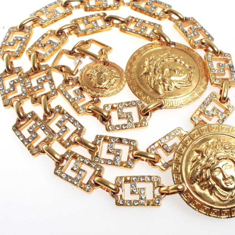 Iconic gold toned Versace medusa head medallion chain belt with diamante detailing. Adjustable sizing with hook fastener. Circa early 1990's. Made in Italy.