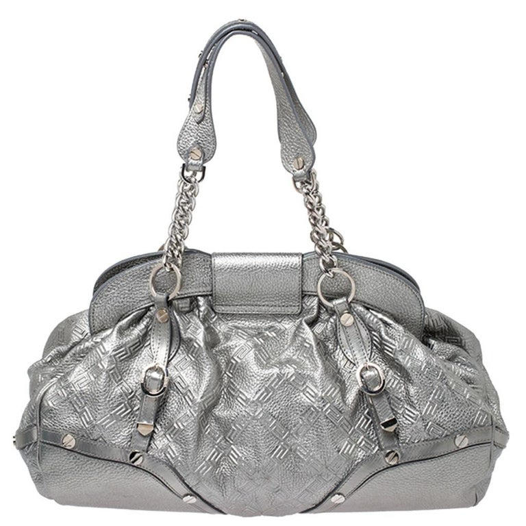 Designed in a unique and wonderful silhouette, this satchel from Versace will be a special addition for any closet. It is crafted from metallic silver leather and is accented with studs on the exterior along with a flap pocket at the front. The bag