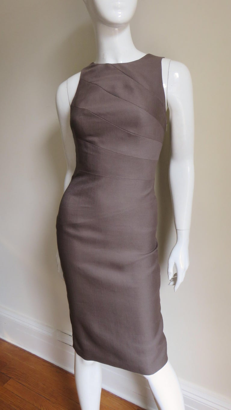 A body conscious dress in a brown light weight silk/wool blend from Versace.  It has a crew neckline forming shoulder straps at the upper back.  The dress is fitted via seams wrapping around it's circumference though to the hem which has a back kick