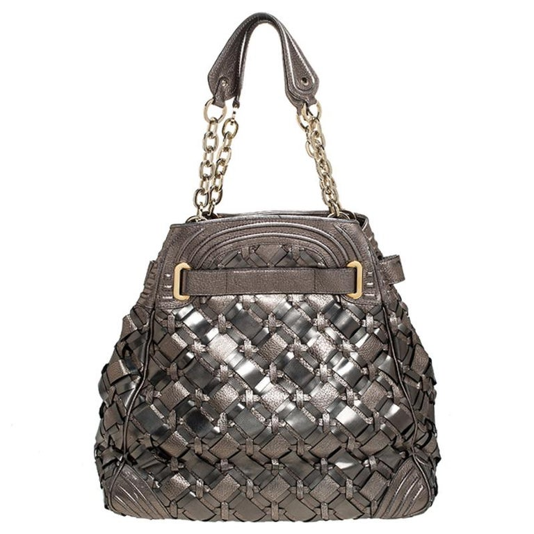 This stunning shoulder bag by Versace makes a statement. It is crafted in Italy and is made from PVC and leather. It comes in a stunning shade of olive green and has a sheen as well. The exterior of the bag is beautified with woven detailing. The