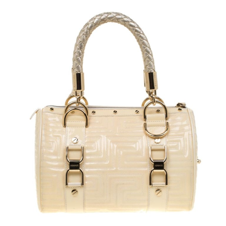 How gorgeous is this satchel from Versace! It carries a grand design and a fabulous interplay of leather and gold-tone hardware. It has a top leading to a fabric interior while being held by two woven handles. The quilts and the brand logo on the