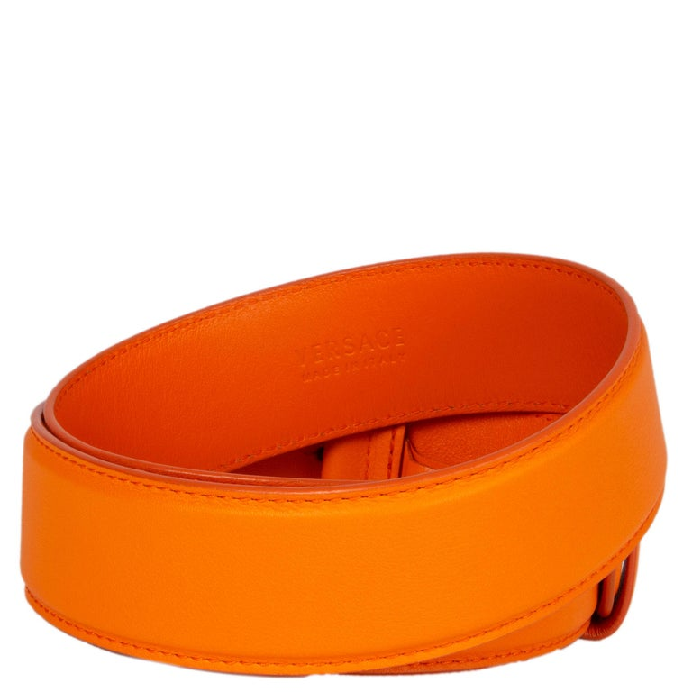 Versace belt in orange calfskin with a round gold- and silver-tone medusa metal buckle. Has been worn and is in excellent condition.   Tag Size 75 Width 4cm (1.6in) Fits 70cm (27.3in) to 80cm (31.2in) Length 89cm (34.7in) Buckle Size Height 5cm