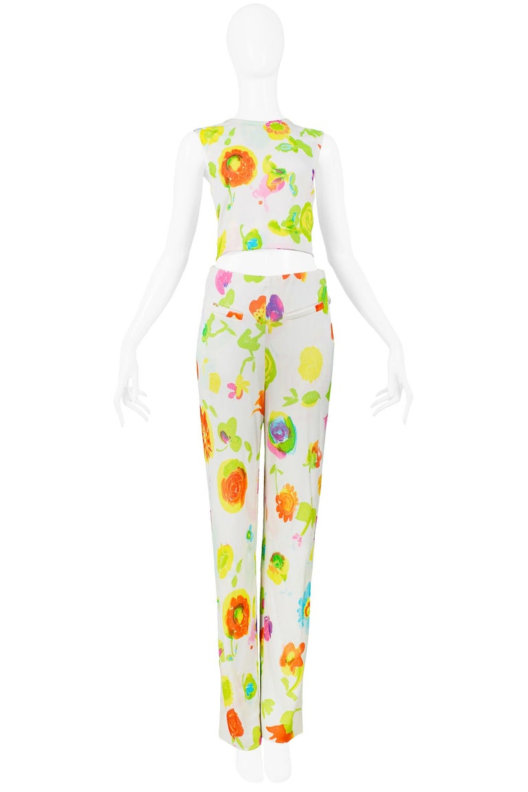 Resurrection Vintage is excited to offer a vintage Versace white and multicolor floral sleeveless top and pants ensemble designed by Gianni Versace. The crop top features an overall floral print and center back zipper. The hip-hugger pants feature