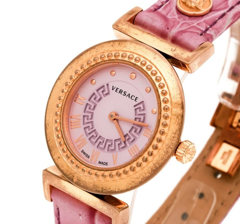 Accessorize your wrist in this luxuriously designed Vanity wristwatch by Versace. It features a round gold-tone stainless steel case and a riveted bezel. The watch has a purple dial with Roman numerals and rivets for hour markers. The watch fixes on