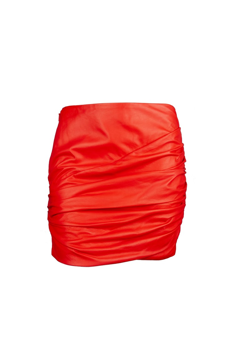 This Versace red mini skirt features asymmetric ruching, lambskin leather and a side zip fastening. The soft red leather is perfect for a bold statement. To recreate the runway look, pair it with the blue leather top also available at our store.