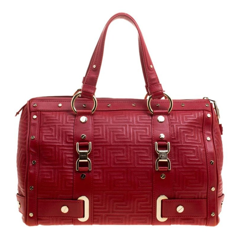 How gorgeous is this satchel from Versace! It carries an outstanding design and a fabulous interplay of red leather and gold-tone hardware. It has a top zipper leading to a satin interior while being held by two handles. The quilt detailing and the