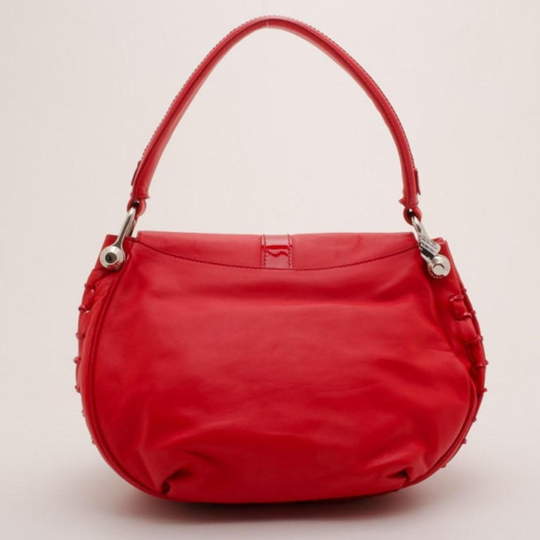Spice up your wardrobe with this fiery red rounded flap shoulder bag by Versace. Crafted from soft leather in a dark shade of red, the flap front is detailed with an intriguing patent leather design. The exterior is also accented with wide patent