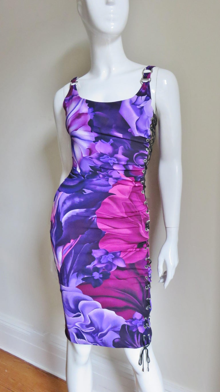 A great flower pattern stretch silk dress in pinks, purples and black.  It has a scoop neckline in the front with metal ring decorated straps.  It is fitted with ruching emanating from from the left side across the dress front and back.  The left