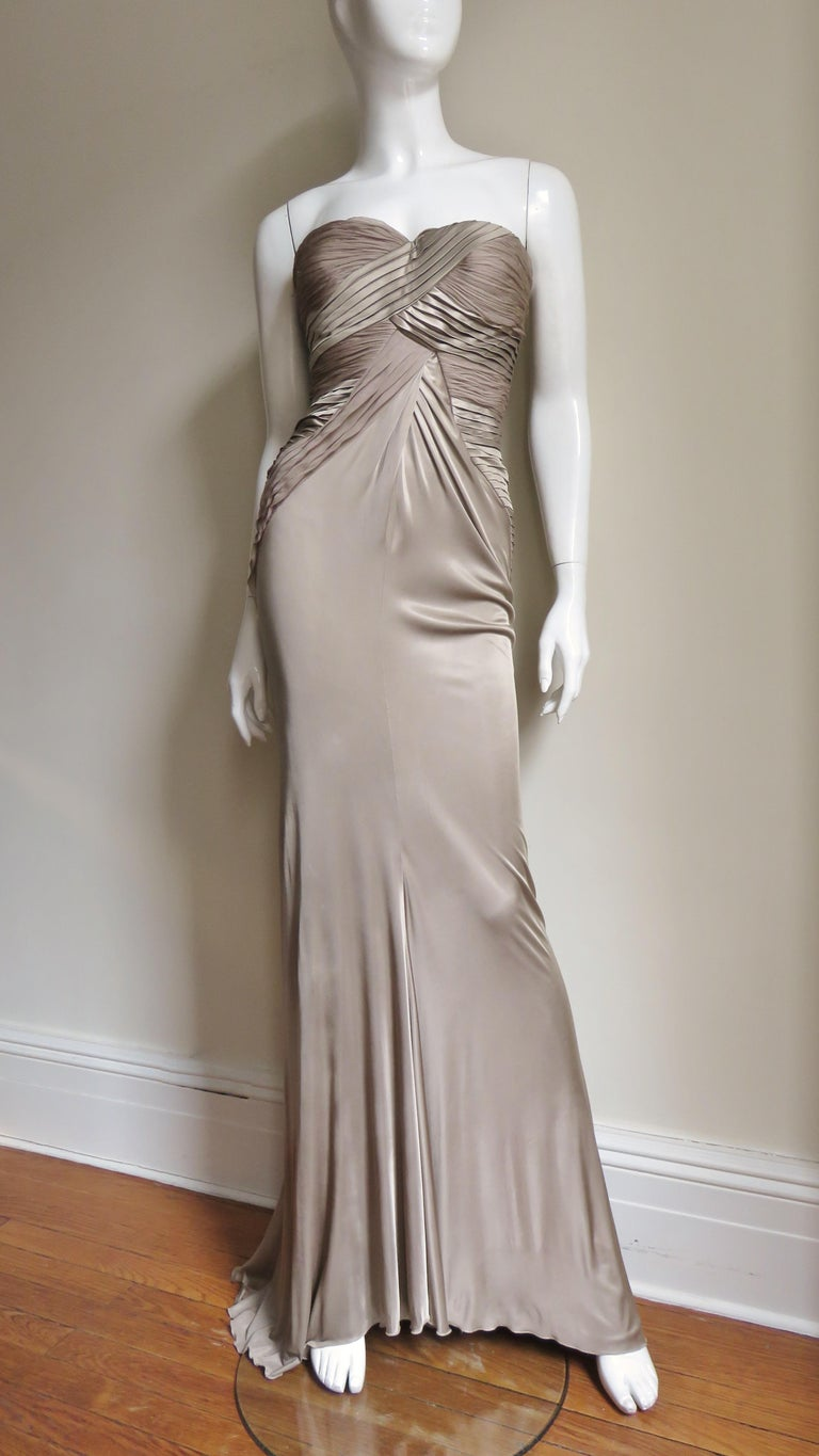 A beautiful light taupe fine knit silk gown from Versace.  It is strapless with molded cups, a boned bodice and panels of finely pleated silk crossing the bust in the front, along the sides and in a thatched pattern at the back to just below the