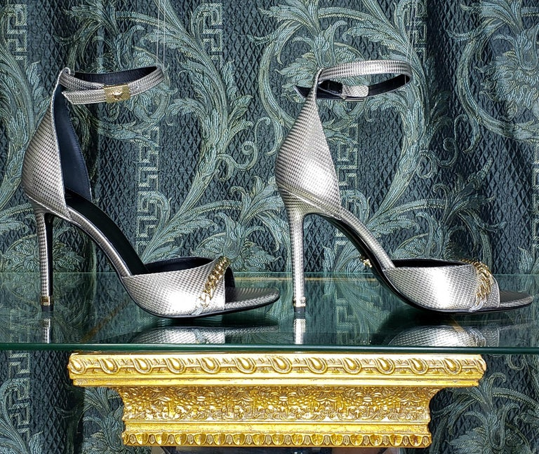 VERSACE  Silver-tone heeled sandals from Versace  Made of textured calf leather  Strap around the ankle with buckle fastening  Gold-tone hardware with 3D Medusa  Decorative chain on the front. Black leather sole  Content: 100% Leather
