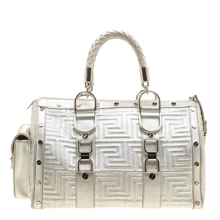 This bold and eye-catching Versace Snap Out Of It satchel is sure to make heads turn. Crafted from silver quilted leather, the bag is accented with a Gianni Versace Couture plate and silver-tone studded hardware. It features dual top braided