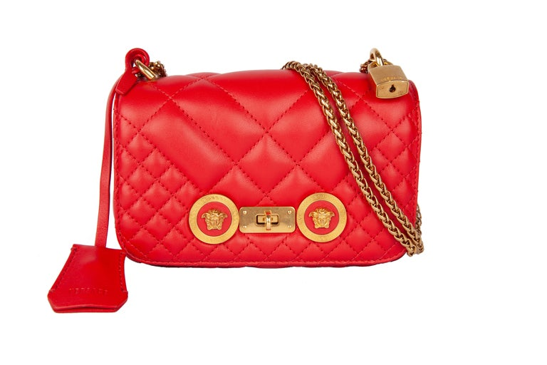 This Versace small red icon shoulder bag features quilted calf leather, gold tone chain and hardware, a flap with medusa studs, a twist clasp, and one main compartment with a slip pocket. The small icon shoulder bag is both functional and