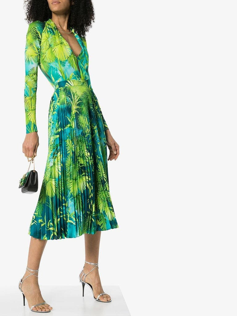 Versace Spring 2020 Verde Jungle Print Pleated High Rise Midi Skirt  Plant this green Jungle print pleated midi skirt from Versace into your wardrobe and button up into the beauty when you're in the mood to make your coworkers green with envy. You'd