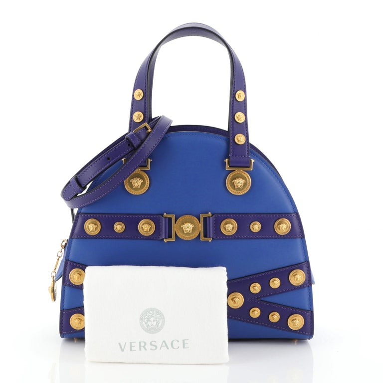 This Versace Tribute Medallion Handbag Leather Medium, crafted from blue leather, features dual leather handles, medallion accents, and gold-tone hardware. Its zip closure opens to a blue leather interior.   Estimated Retail Price: $2,995 Condition: