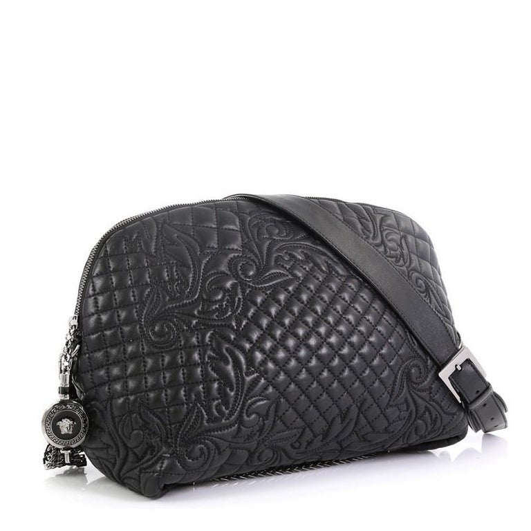 This Versace Vanitas Crossbody Bag Barocco Leather, crafted from black barocco leather, features an adjustable strap, enameled medusa charm, fringe tassels, and gunmetal-tone hardware. Its zip closure opens to a blue satin interior with slip
