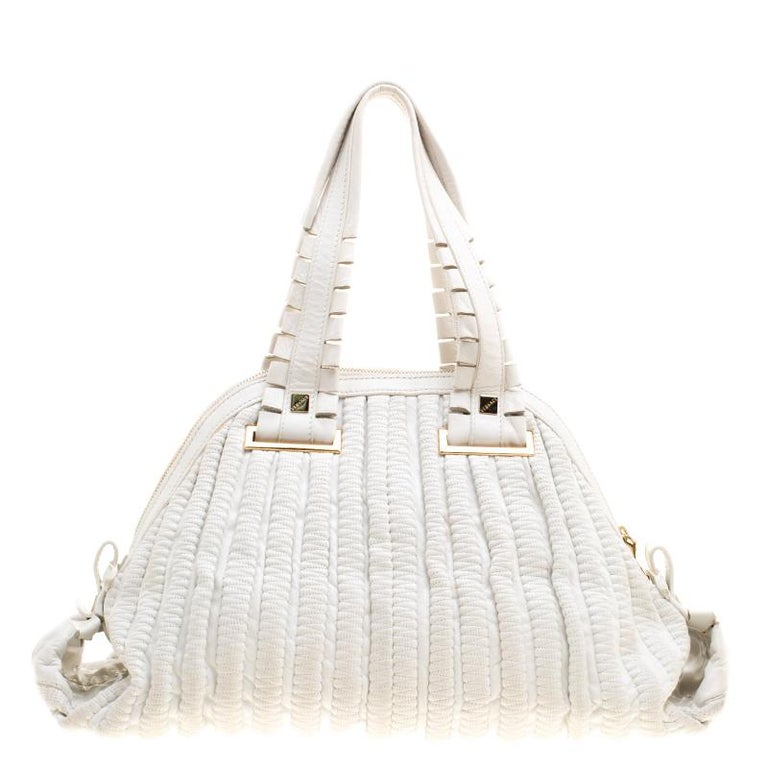 Crafted from white leather, this dome satchel by Versace features a beautiful pattern on the exterior along with folded edges and gold-tone logo plaque at the center. Equipped with creatively made dual top handles, protective metal feet at the