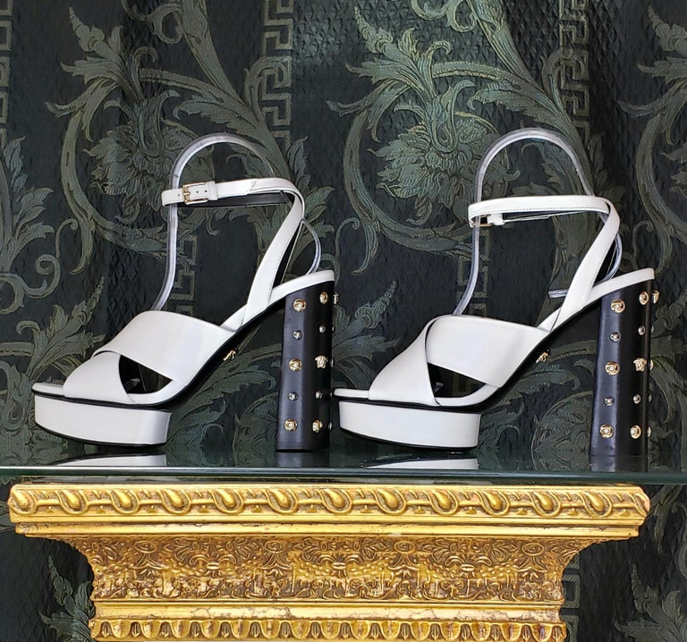 VERSACE  White leather sandals shoes with gold and silver studs and famous Medusa Studs  DETAILS:  Open toe and heel  Buckling ankle strap closure  Content: 100% Leather (Lining and Sole)       Color: White  Heel: 5 1/8 inches  Platform: 1 inch
