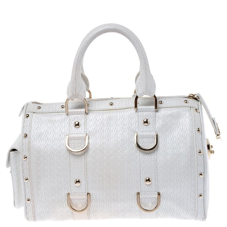 This white leather bag is the ideal pick for all your essentials. The satin lining of this bag is well-sized to house all your essentials. Made of superior quality, this studded Versace bag boasts of style and luxury.  Includes: The Luxury Closet