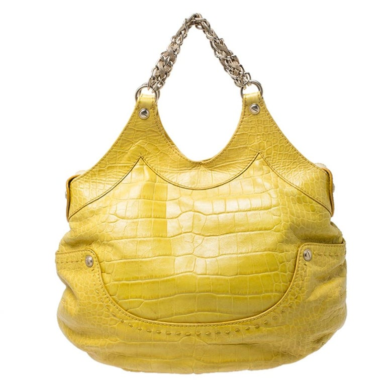 This Kiss satchel by Versace is stunning and exudes style. It is crafted in Italy and is made of crocodile embossed leather. It comes in a bright shade of yellow and makes an absolute statement. It comes with dual chain-link handles, an open-top