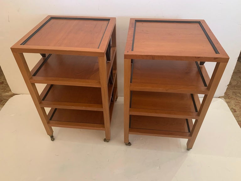 Great looking pair of square 4 tier ebony and fruitwood side or end tables having handsome color contrast and brass casters.