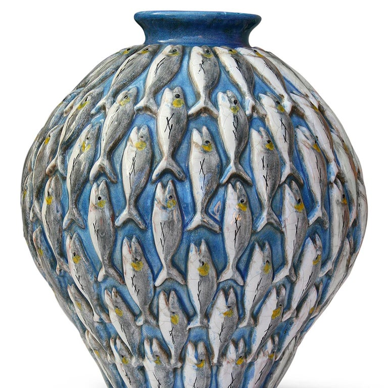 A school of fish swims upwards in the decoration of this elegant vase. Masterfully hand painted, the iridescent fish are seemingly in relief against the blue background, their delicate profiles highlighting the sinuous curve of the vase tapering to