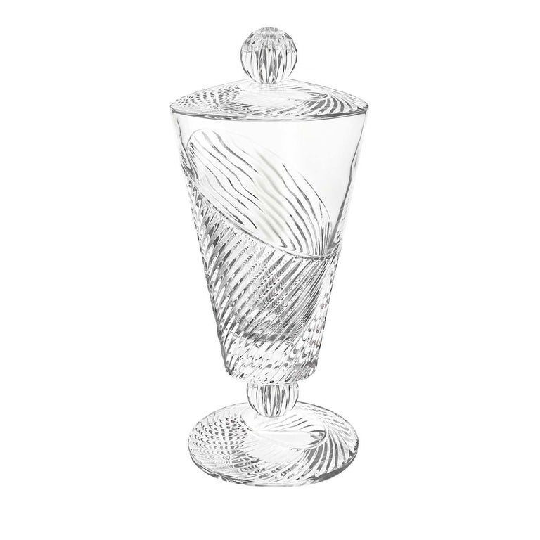 Part of the Vertigo collection, this vase with lid was crafted of transparent glass and features a footed shape and a conical bowl. The smooth surface of the piece is adorned with an etched decoration that boasts a dynamic tension thanks to a series