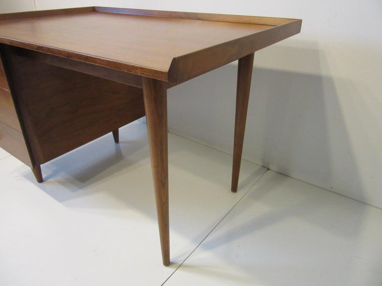 A smaller sized dark walnut single pedestal desk with three angled side drawers , and raised edges to the sides and back of the top having a compartment and pen holder to the top drawer . A well crafted and designed piece from the iconic Mid Century