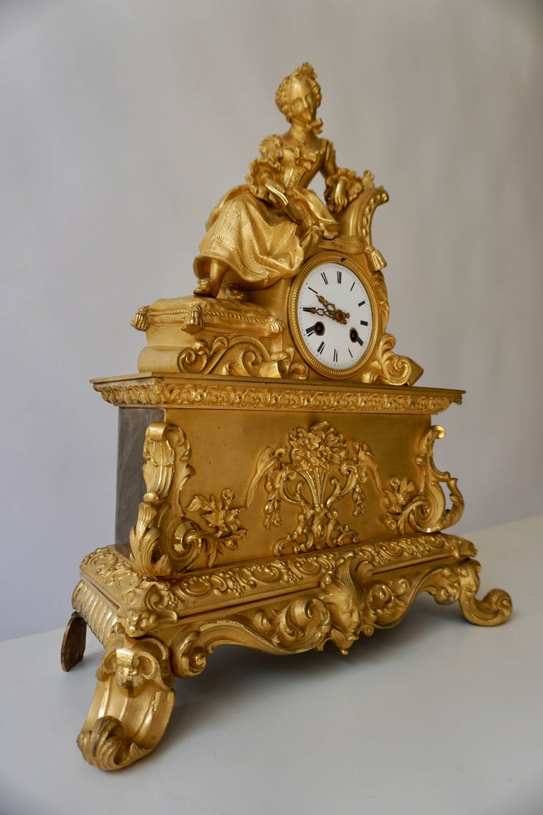 A very fine and elegant fire, gilt bronze mantle clock in the romantic taste, the base resting on scroll feet connected with leafy volutes centered by a female mask under a decorated frieze showing animal heads on the corners, the pediment with a