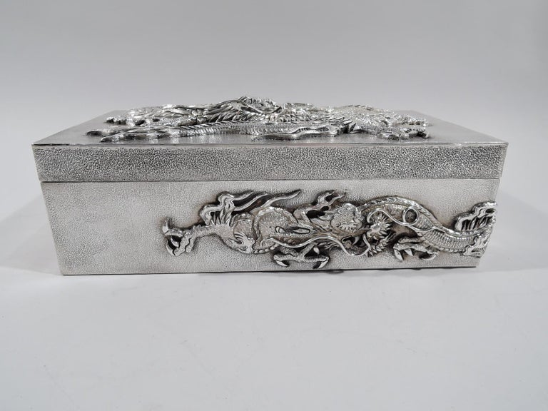 Large Japanese silver box, circa 1910. Rectangular with straight sides and hinged cover. all-over stippling. On cover is applied a dragon, all scales, fangs, and talons with slithering serpentine body. Same two wraparound sides. Fearsome protectors