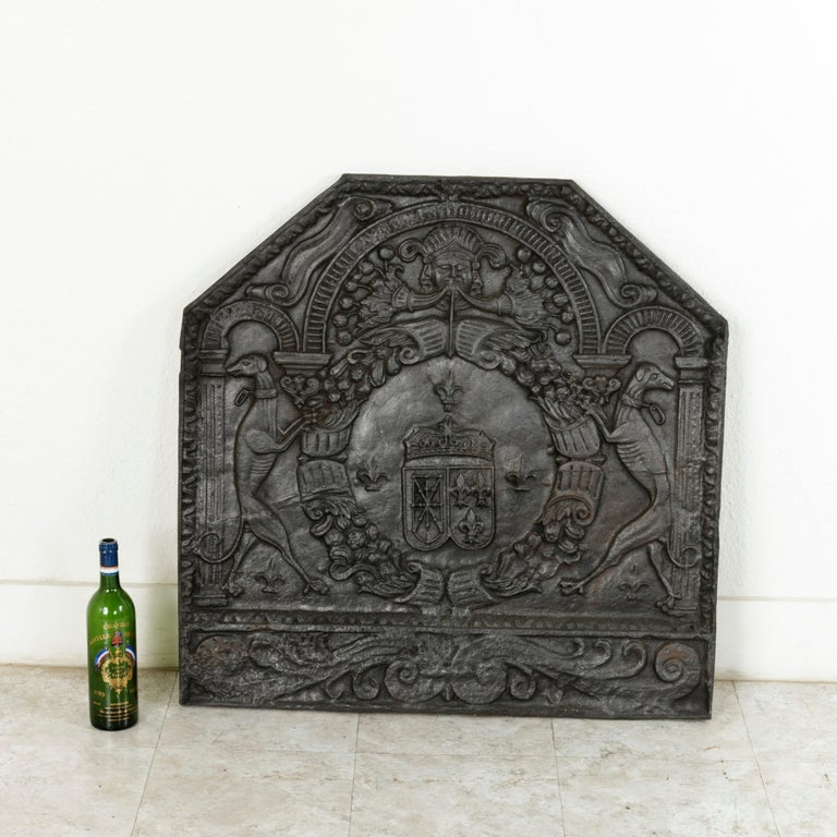 Measuring nearly 34 inches square, this very large mid-18th century French Louis XV period iron fireplace back features a heraldic motif with the coats of arms of France and Navarre side by side in the centre with a crown above. A symbol of the