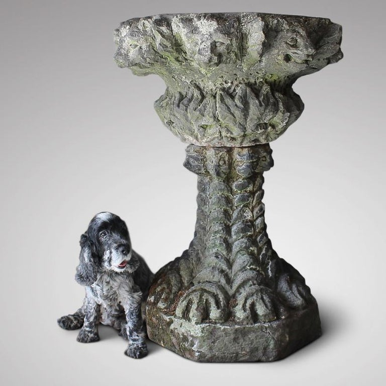 A rare and large, 19th century, carved sandstone gothic grotto urn, beautifully weathered and lichen encrusted, with a border of grotesque animal faces around the top of the bowl and base.