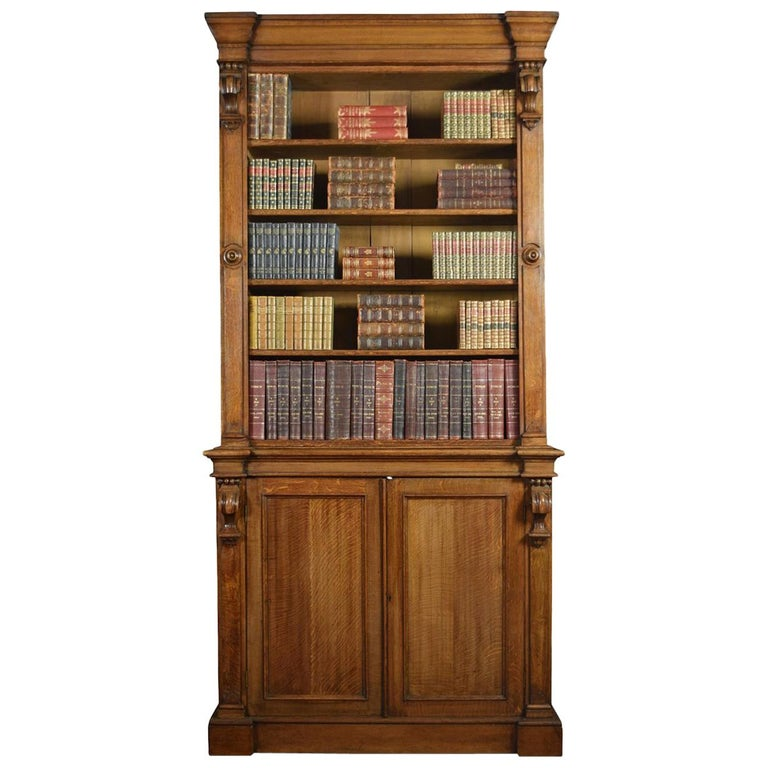 19th century oak bookcase with a flared cornice over a large open top bookcase with four adjustable shelves, the base section fitted with two panelled doors enclosing shelved interior. All raised up on plinth base Dimensions: Height 103.5