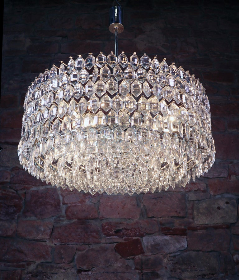 Spectacular huge cluster with numerous faceted crystals arranged in six rows on a silver plated frame. Chandelier illuminates beautifully and offers a lot of light. Gem from the time. With this light you make a clear statement in your interior