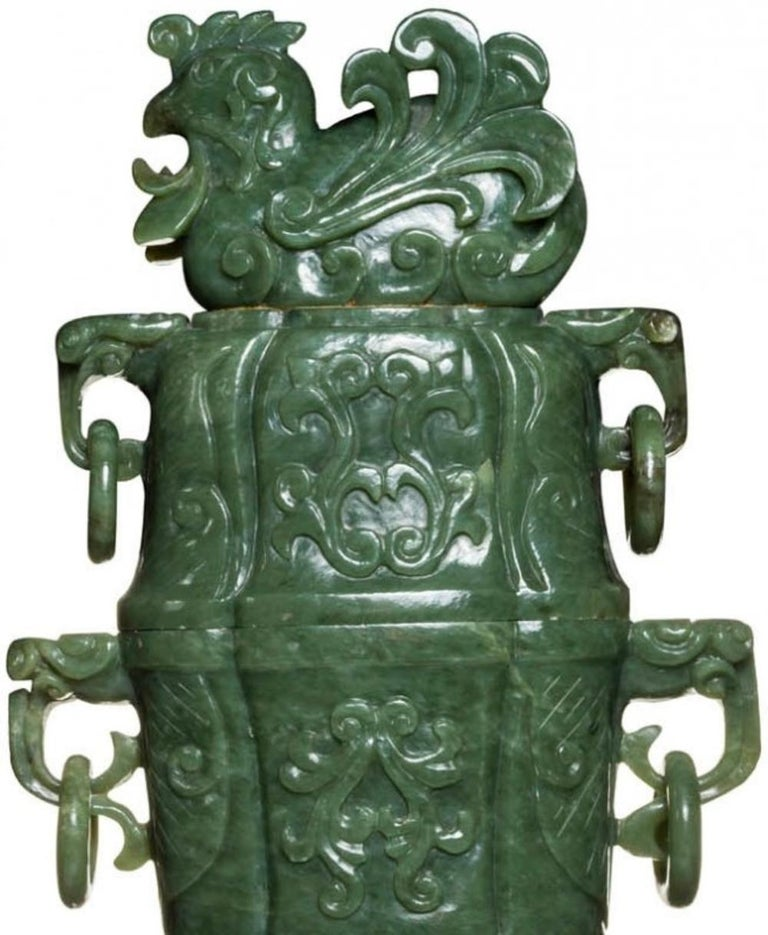 Very large Chinese carved jade vases and covers Each carved in relief with scroll detail, flanked by mask Handles supporting loose rings, the conforming cover flanked by loose rings and surmounted by a bird finial. Measures: Height 28 in. (71.12