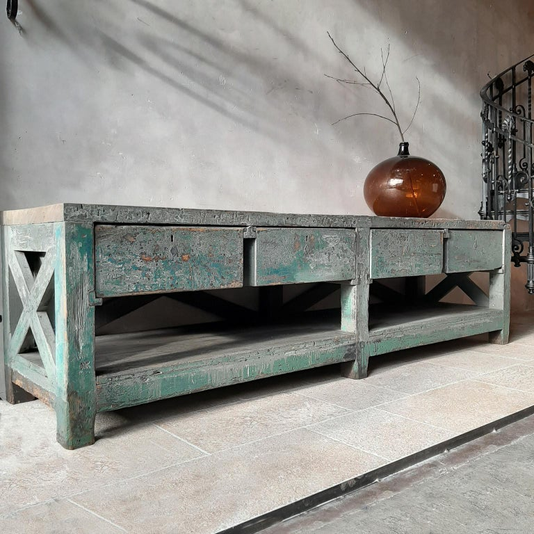 Very large Dutch workbench from the 1950swith original old paint remnants. A beautiful and very strong pine construction with diagonal crosses and 4 deep drawers. This workbench with original old green patina remains can beautifully serve as a