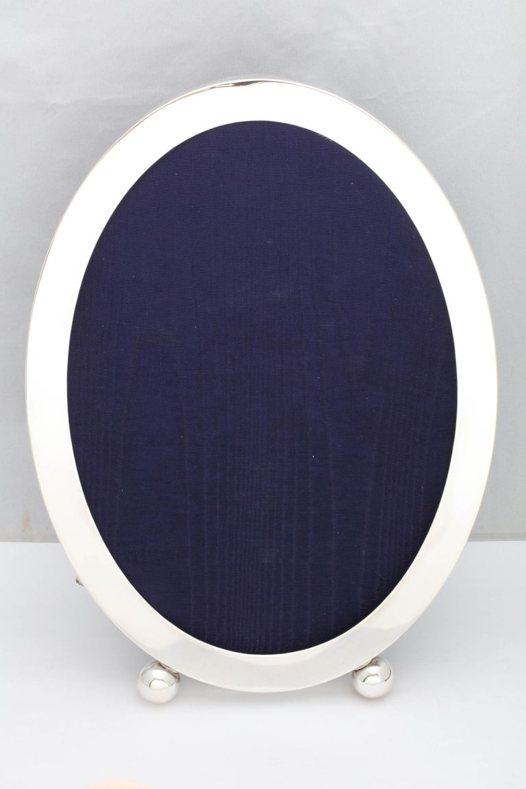 Very large, Edwardian, sterling silver oval picture frame on ball feet, Gorham Manufacturing Co., Providence, Rhode Island, circa 1910. Back is dark blue velvet. Measures 14 3/4 inches high x 10 inches wide x 6 1/4 inches deep when easel is in open